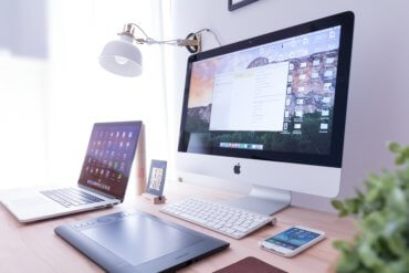 designer's desk with macbook, iphone and imac with productivity tool on screen